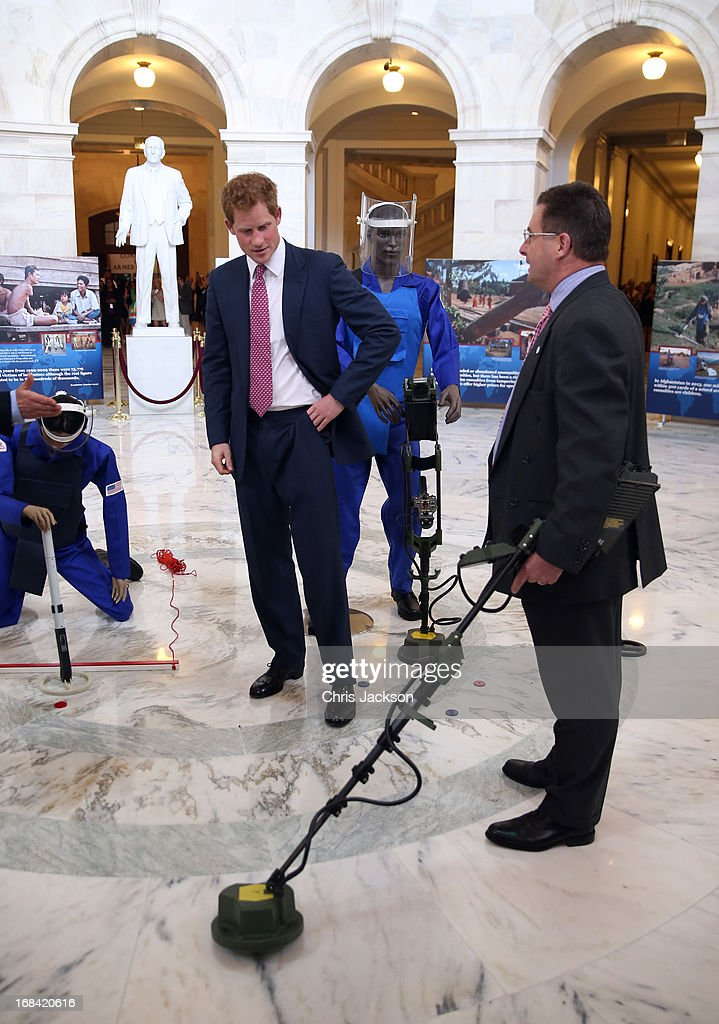 Prince Harry (C) tours an anti-landmine photography exhibition by The HALO Trust charity during the first day of his visit to the United States at the Russell Senate Office Building on May 9, 2013 in Washington, DC. HRH will be undertaking engagements on behalf of charities with which the Prince is closely associated on behalf also of HM Government, with a central theme of supporting injured service personnel from the UK and US forces.