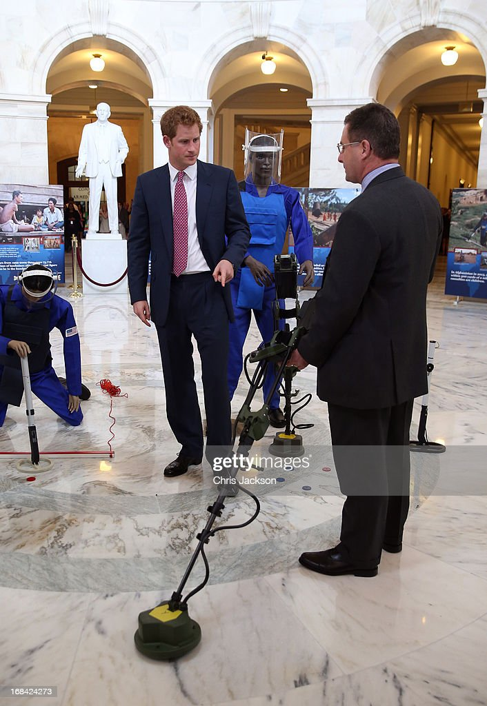 Prince Harry (L) tours an anti-landmine photography exhibition by The HALO Trust charity during the first day of his visit to the United States at the Russell Senate Office Building on May 9, 2013 in Washington, DC. HRH will be undertaking engagements on behalf of charities with which the Prince is closely associated on behalf also of HM Government, with a central theme of supporting injured service personnel from the UK and US forces.