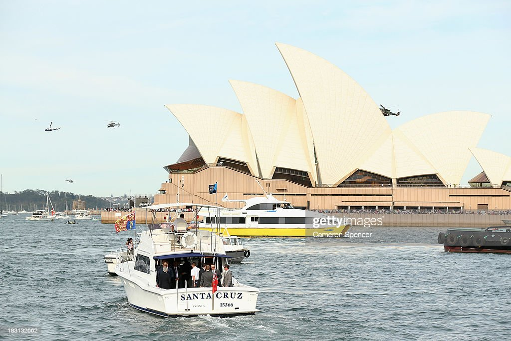 Prince Harry travels in a boat past the Sydney Opera House bound for Kirribilli during the International Fleet Review on October 5, 2013 in Sydney, Australia. Over 50 ships participate in the International Fleet Review at Sydney Harbour to commemorate the 100 year anniversary of the Royal Australian Navy's fleet arriving into Sydney. Prince Harry is an official guest of the Australian Government and will take part in the fleet review during his two-day visit to Australia.