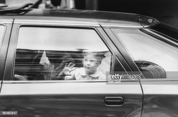 Prince Harry w hand to window of car looking out window w William in bkgrd prob London England
