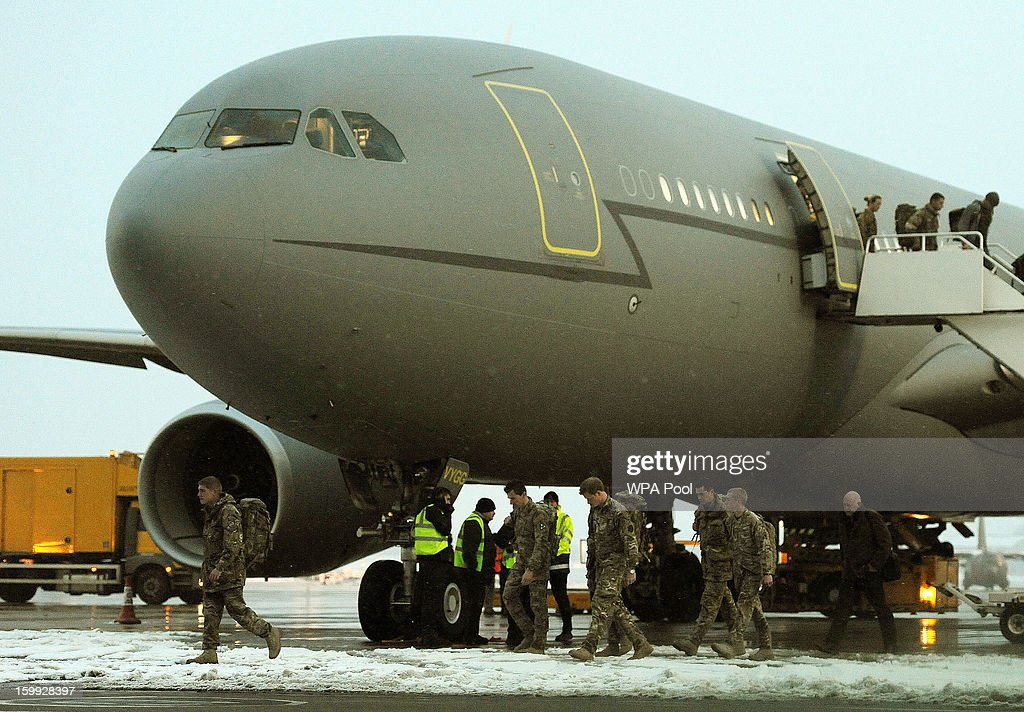 Prince Harry (4th R) walks after disembarking from a Royal Air Force A-330 transport aircraft as he arrives at RAF Brize Norton on January 23, 2013 in Oxfordshire, England. The prince is arrving back in the UK following the completion of his 20 week tour of duty in Afghanistan as an Apache Helicopter Pilot/Gunner with 662 Squadron of the Army Air Corps.