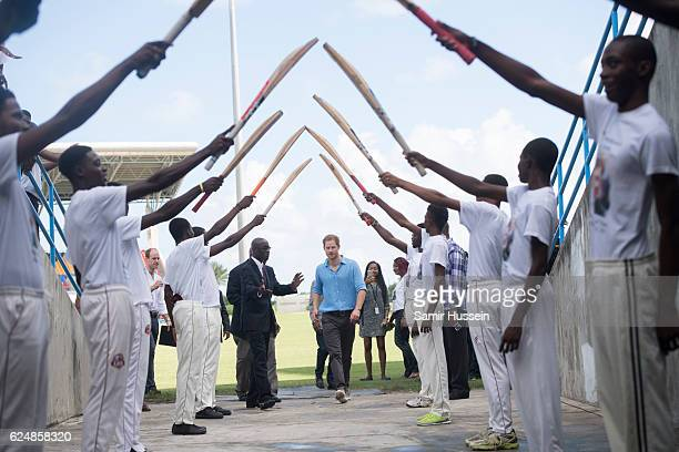 Prince Harry walks through a guard of honour during a Youth Sports Festival at the Sir Vivian Richards Stadium on the second day of an official visit...