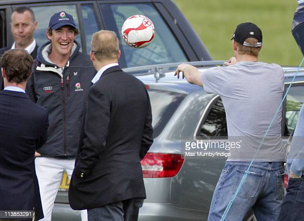 Prince Harry warms up by throwing and catching a football before playing in the Audi Polo Challenge polo match for team Sentebale versus team Audi at...