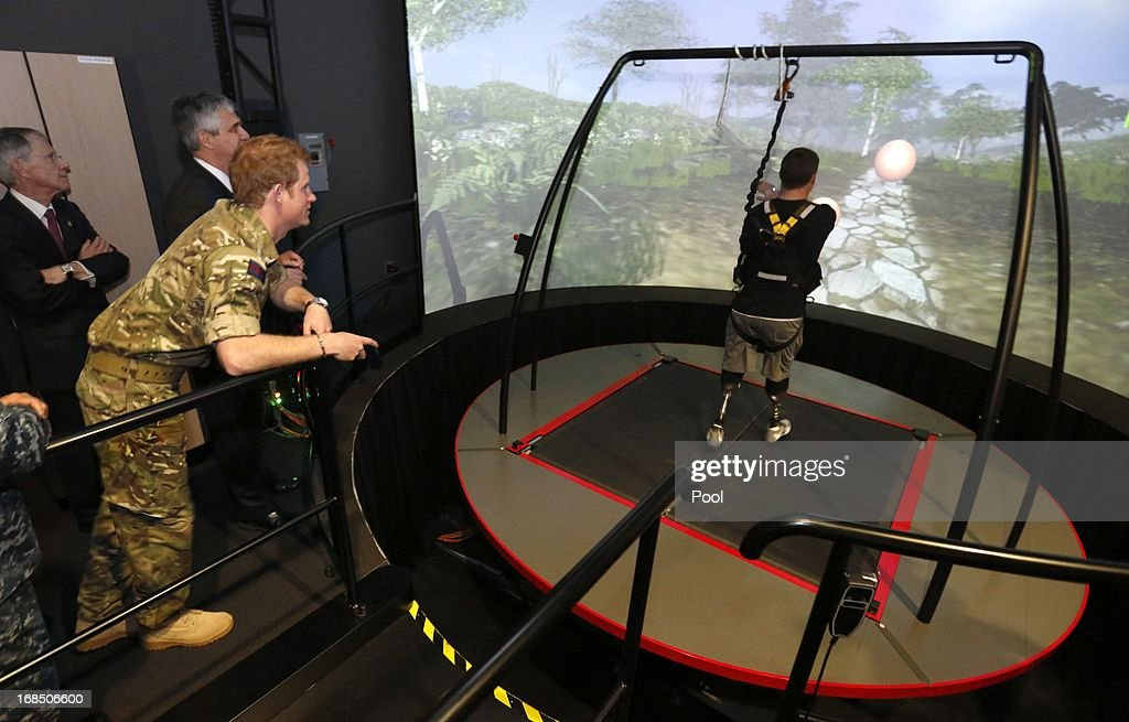 Prince Harry watches as a wounded soldier walks on prosthetic legs whilst using a treadmill during his visit to the Military Advanced Training Center at Walter Reed National Military Medical Center treating wounded soldiers undergoing physical therapy on May 10, 2013 in Bethesda, Maryland. HRH will be undertaking engagements on behalf of charities with which the Prince is closely associated on behalf also of HM Government, with a central theme of supporting injured service personnel from the UK and US forces.