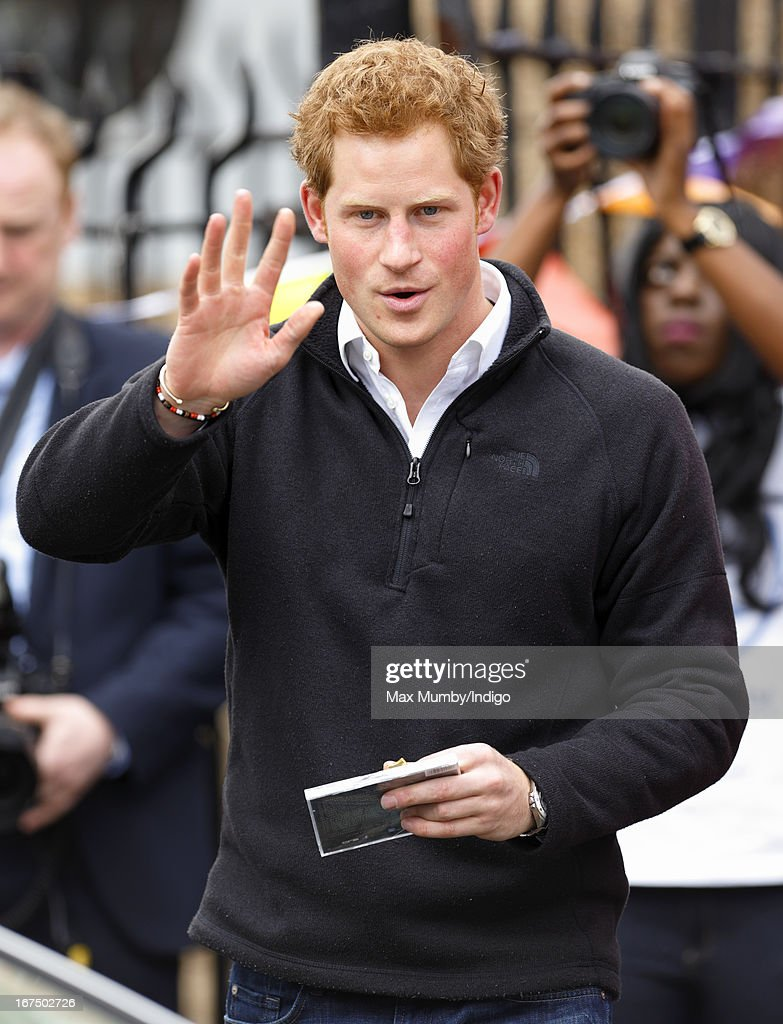 Prince Harry waves as he leaves the Russell Youth Club during a day of engagements in Nottingham on April 25, 2013 in Nottingham, England.