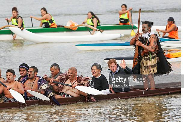 Prince Harry waves to onlookers while paddling a waka on the Whanganui River during a visit to Putiki Marae on May 14 2015 in Wanganui New Zealand...