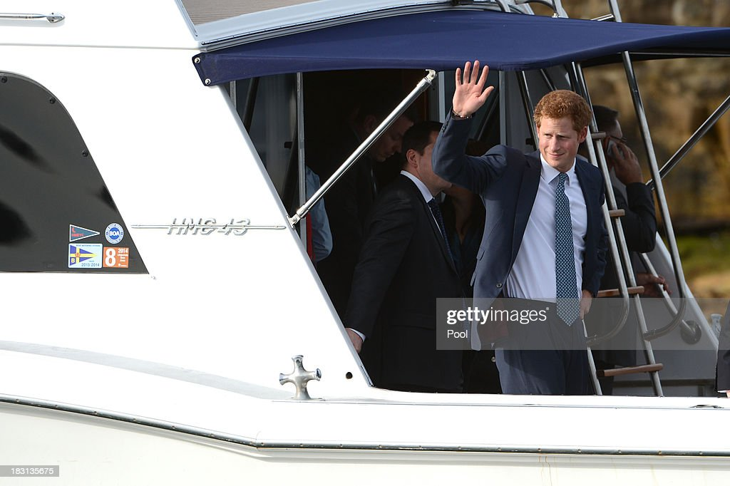 Prince Harry waves to the crowds lining Sydney Harbour from the motor cruiser Santa Cruz as he makes his way to Kirribilli for a function with Prime Minister Tony Abbott at Kirribilli House, on October 5, 2013 in Sydney, Australia. Over 50 ships participate in the International Fleet Review at Sydney Harbour to commemorate the 100 year anniversary of the Royal Australian Navy's fleet arriving into Sydney. Prince Harry is an official guest of the Australian Government and will take part in the fleet review during his two-day visit to Australia.
