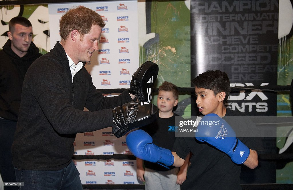 Prince Harry wears boxing pads as eleven-year-old Shabaz punches during a visit to the KK Boxing Club on April 25, 2013 in Nottingham, England.