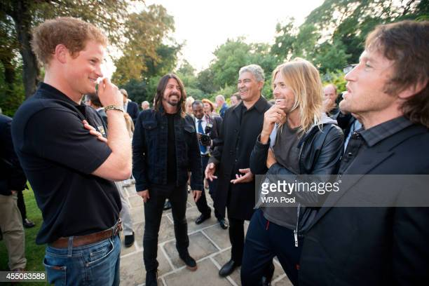 Prince Harry with singer Dave Grohl and drummer Taylor Hawkins of the Foo Fighters attend an Invictus Games Reception at the American Ambassador's...