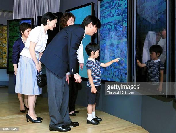 Prince Hisahito touches the display while Prince Akishino and Princess Kiko of Akishino smile during their visit to an art exhibition at Suntory...