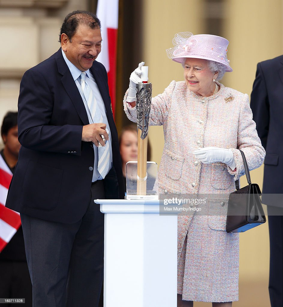 Prince Imran of Malaysia, President of the Commonwealth Games Federation, looks on as Queen <a gi-track='captionPersonalityLinkClicked' href=/galleries/search?phrase=Elizabeth+II&family=editorial&specificpeople=67226 ng-click='$event.stopPropagation()'>Elizabeth II</a> places her hand-written message to the Commonwealth into the 2014 Glasgow Commonwealth Games Baton during the launch of the Queen's Baton Relay at Buckingham Palace on October 9, 2013 in London, England.