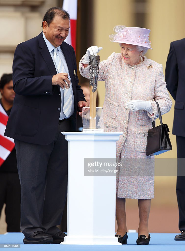 Prince Imran of Malaysia, President of the Commonwealth Games Federation, looks on as Queen <a gi-track='captionPersonalityLinkClicked' href=/galleries/search?phrase=Elizabeth+II&family=editorial&specificpeople=67226 ng-click='$event.stopPropagation()'>Elizabeth II</a> places her hand-written message to the Commonwealth into the 2014 Glasgow Commonwealth Games Baton during the launch of the Queen's Baton Relay at Buckingham Palace on October 9, 2013 in London, England. Following the launch, the baton relay will continue it's journey visiting all 70 competing nations and territories ahead of the 2014 Glasgow Commonwealth Games.