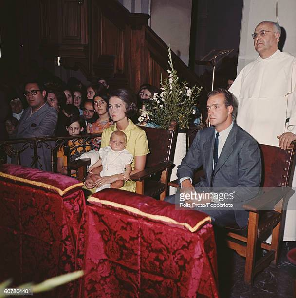 Prince Juan Carlos later Juan Carlos I of Spain pictured sitting with his wife Sophia of Greece and Denmark later Queen Sofia of Spain and baby...