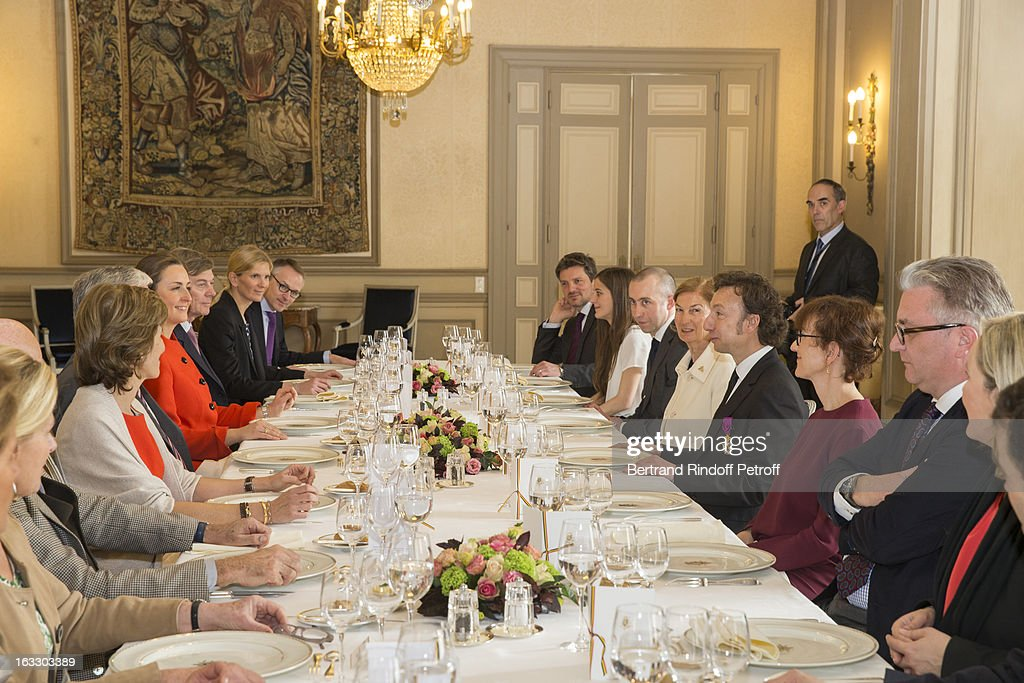 Prince Laurent of Belgium (2nd R), French journalist and author Stephane Bern (3rd R), Princess Claire of Belgium (5th L) and guests prepare to share a meal after Bern was appointed officer in the King Leopold order during a ceremony at Palais d'Egmont on March 7, 2013 in Brussels, Belgium.
