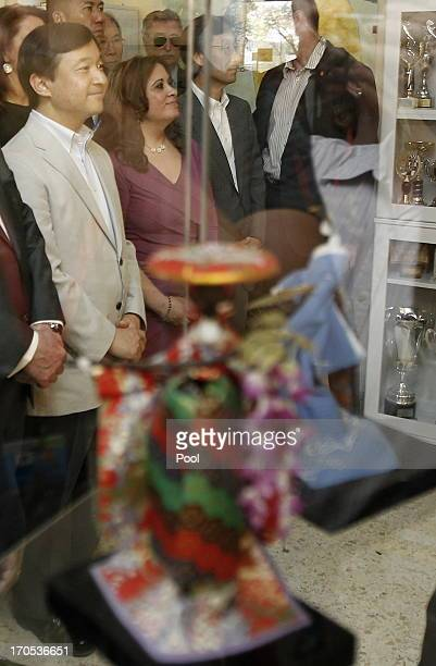 Prince Naruhito of Japan listens to a Japanese song 'Hana wa Saku' as he visits a classroom at Vicente Neria in Coria del Rio on June 14 2013 in...