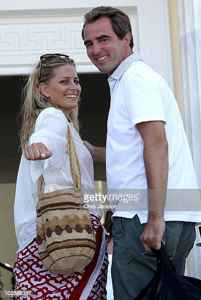 Prince Nikolaos and his fiance Tatiana Blatnik wave from the steps of the Poseidon Hotel as they arrive in advance of their prewedding reception on...