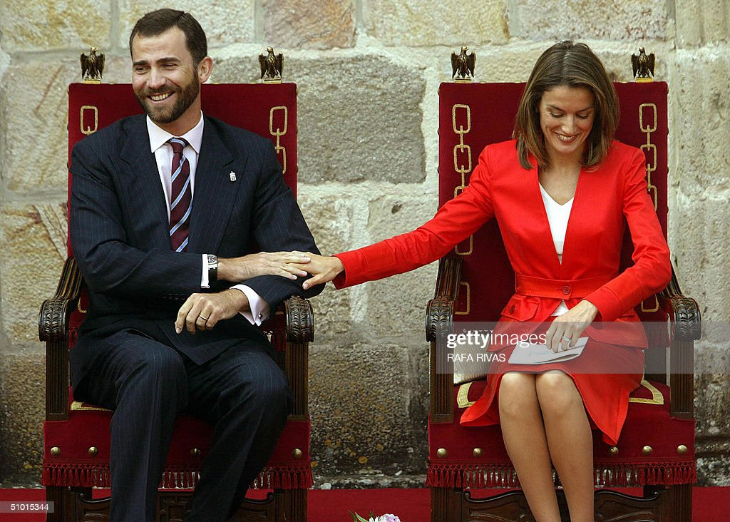 Prince of Asturias Felipe de Borbon (L) and his wife Princess Letizia (R) touch their hands as they attend the 'Prince of Viana' Culture award ceremony, 01 July 2004 at Leyre Monastery, in the northern Spanish village of Yesa, in the Navarra province. The award was given to Spanish architect Fernando Redon. AFP PHOTO / RAFA RIVAS
