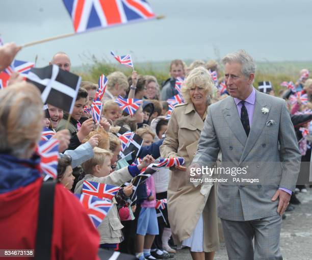 Prince of Wales and Duchess of Cornwall are greeted by children waving flags as they arrive on a windy clifftop at Tintagel Cornwall The Prince and...