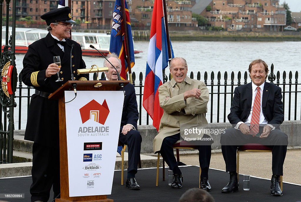 Prince Philip, Duke of Edinburgh and Bill Muirhead (R), Agent General of South Australia, laugh as Honorary Captain Andrew Chapman prepares to throw champagne to the spirits of the four winds during the renaming ceremony for the clipper ship 'The City of Adelaide' on October 18, 2013 in London, England.