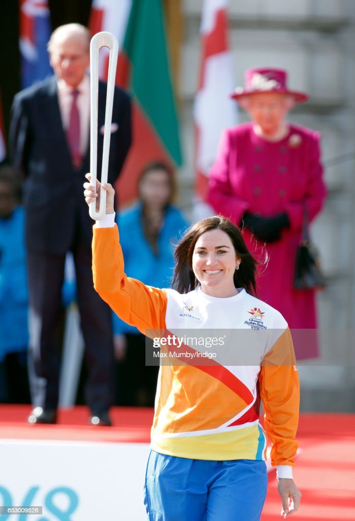 Prince Philip, Duke of Edinburgh and Queen Elizabeth II look on as former track cyclist Anna Meares of Australia holds The Queen's Baton during the launch of The Queen's Baton Relay for the XXI Commonwealth Games being held on the Gold Coast in 2018 at Buckingham Palace on March 13, 2017 in London, England.