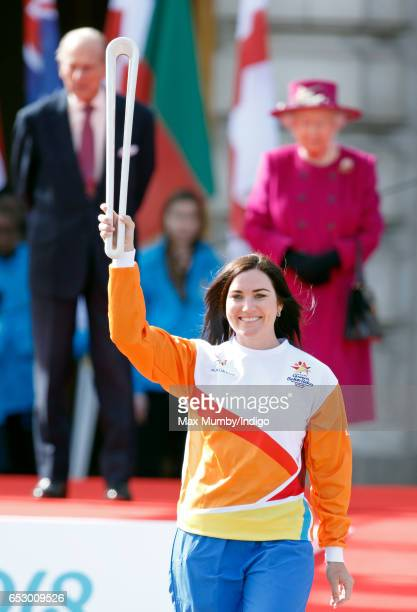 Prince Philip Duke of Edinburgh and Queen Elizabeth II look on as former track cyclist Anna Meares of Australia holds The Queen's Baton during the...