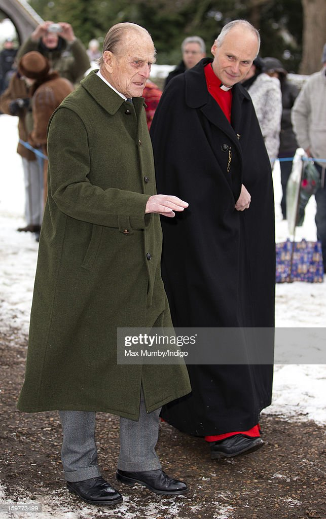 Prince Philip, Duke of Edinburgh and Reverend Jonathan Riviere walk through the snow covered church yard to attend Sunday Service along with Queen Elizabeth II at the Church of St Lawrence in Castle Rising near the Sandringham Estate on January 20, 2013 near King's Lynn, England.