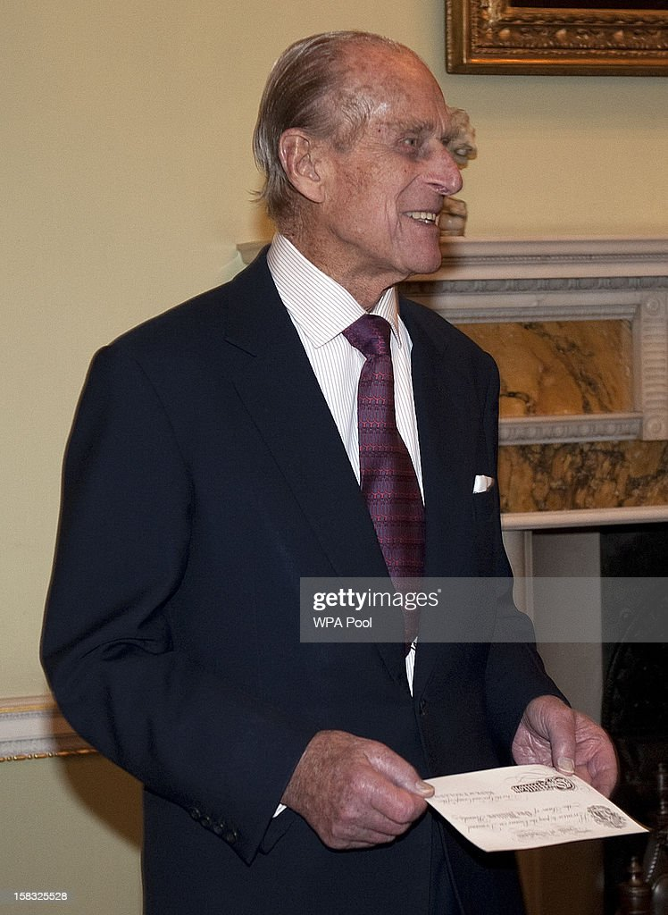 Prince Philip, Duke of Edinburgh holds a bank note as he visits the Bank of England with Queen Elizabeth II on December 13, 2012 in London, England. Governor, Sir Mervyn King met with the Queen and Duke before they visited the Banking Hall to discuss payment system controls. The royal couple viewed banknotes, counterfeit currency, a gold vault, historical items, met with gold experts, security staff and the Market Operations Office while on their visit to the Bank of England.