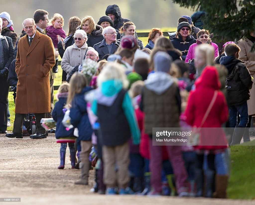 Prince Philip, Duke of Edinburgh (L) looks on as a group of young children queue to present Queen Elizabeth II with flowers as she leaves St. Mary Magdalene Church, Sandringham after attending Sunday service on December 30, 2012 near King's Lynn, England.