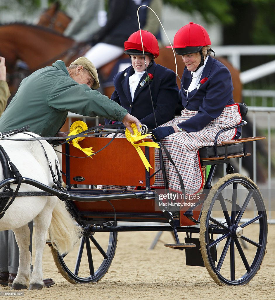 Prince Philip, Duke of Edinburgh presents rosettes to competitors in the Driving for the Disabled competition on day 2 of the Royal Windsor Horse Show on May 9, 2013 in Windsor, England.