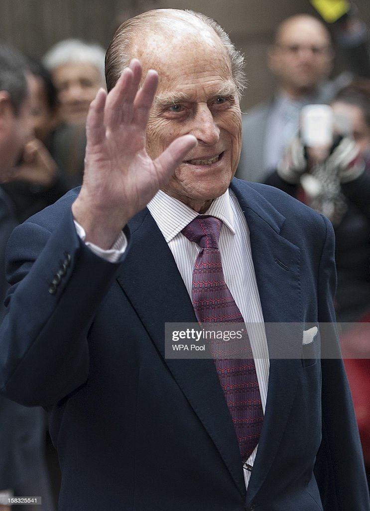 Prince Philip, Duke of Edinburgh waves as he visits the Bank of England with Queen Elizabeth II on December 13, 2012 in London, England. Governor, Sir Mervyn King met with the Queen and Duke before they visited the Banking Hall to discuss payment system controls. The royal couple viewed banknotes, counterfeit currency, a gold vault, historical items, met with gold experts, security staff and the Market Operations Office while on their visit to the Bank of England.