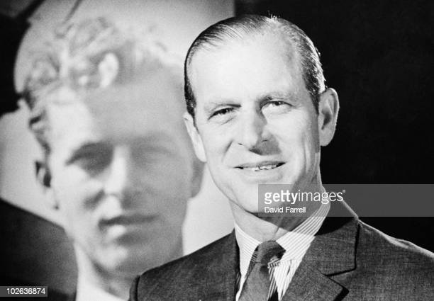 Prince Philip Duke of Edinburgh with a photograph of his younger self circa 1975