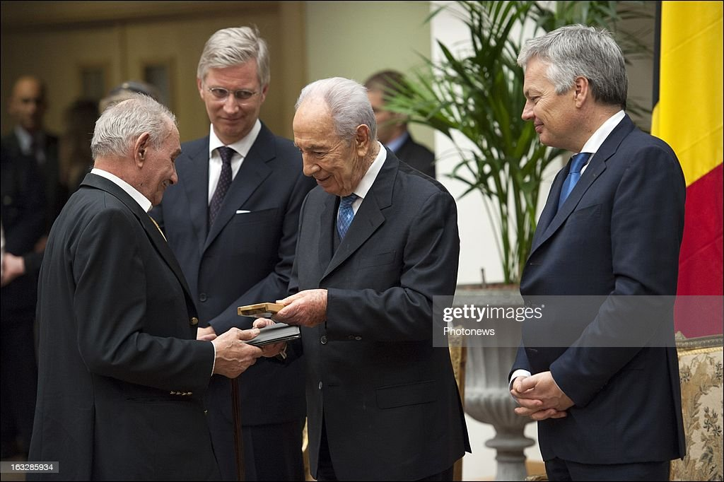 Prince Philip of Belgium (2ndL) with President of Israel Shimon Peres (C) as he presents the decoration of the Righteous Among the Nations to a guest and Minister Didier Reynders (R) on March 5, 2013 in Brussels , Belgium. 11 Belgian families were decorated with the Righteous Among the Nations for saving Jewish citizens during World War II.