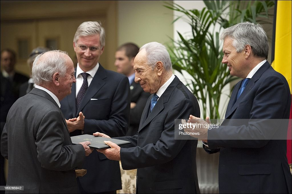Prince Philip of Belgium (2ndL) with President of Israel <a gi-track='captionPersonalityLinkClicked' href=/galleries/search?phrase=Shimon+Peres&family=editorial&specificpeople=201775 ng-click='$event.stopPropagation()'>Shimon Peres</a> (C) as he presents the decoration of the Righteous Among the Nations to a guest and Minister <a gi-track='captionPersonalityLinkClicked' href=/galleries/search?phrase=Didier+Reynders&family=editorial&specificpeople=548982 ng-click='$event.stopPropagation()'>Didier Reynders</a> (R) on March 5, 2013 in Brussels , Belgium. 11 Belgian families were decorated with the Righteous Among the Nations for saving Jewish citizens during World War II.