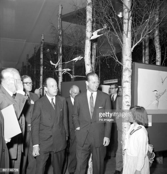 Prince Philip The Duke of Edinburgh looks at one of the displays done by a young girl during his tour of the Wildlife Exhibition at the Royal...