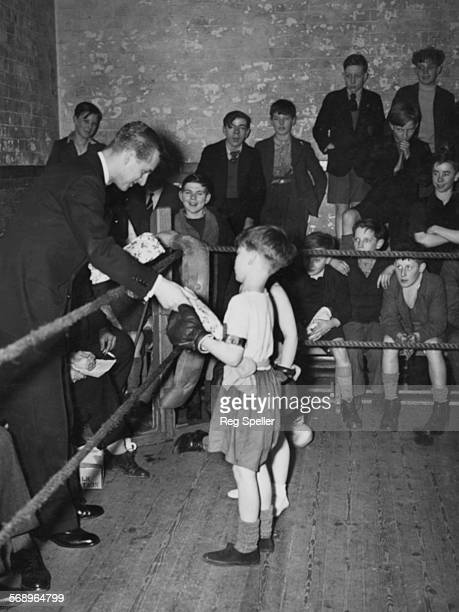 Prince Philip the Duke of Edinburgh presenting two young boys with gifts following their boxing match during a visit to the Canterbury Club in Kent...
