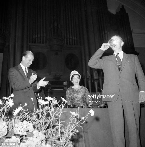 Prince Philip The Duke of Edinburgh smiles and applauds as Mr Harvey Antrobus quaffs half a pint of milk from the Merrik Burrell Tankard at the AGM...