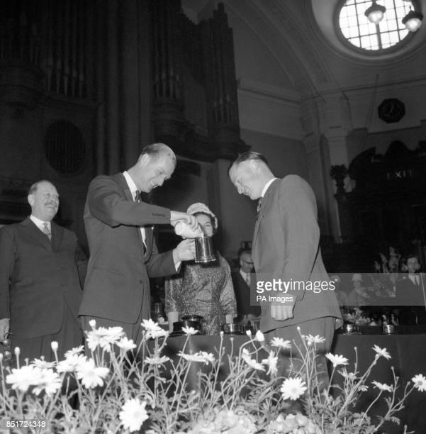 Prince Philip the Duke of Edinburgh smilingly pours half a pint of milk into the Merrik Burrell Tankard before handing it to Mr Harvey Antrobus at...