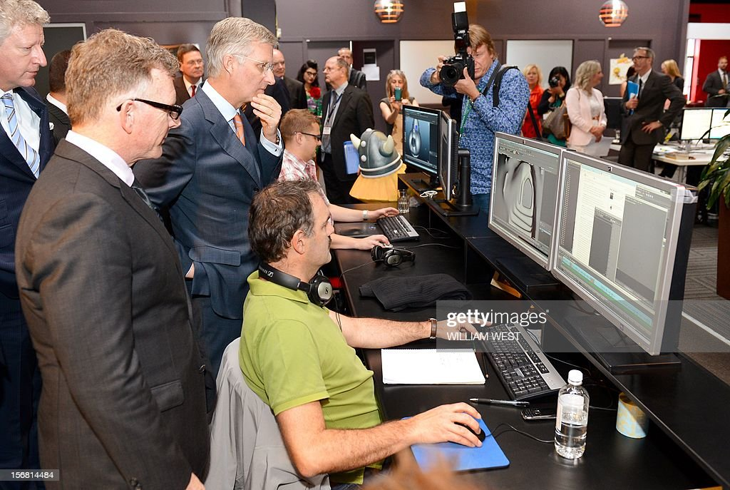Prince Philippe of Belgium (3/L) looks at the animation on the screens as he talks to members of the creative team during a tour of Flying Bark Productions in Sydney on November 22, 2012. Philippe is on an 11-day mission to Australia and New Zealand to strengthen economic and trade ties.. AFP PHOTO/POOL/William WEST