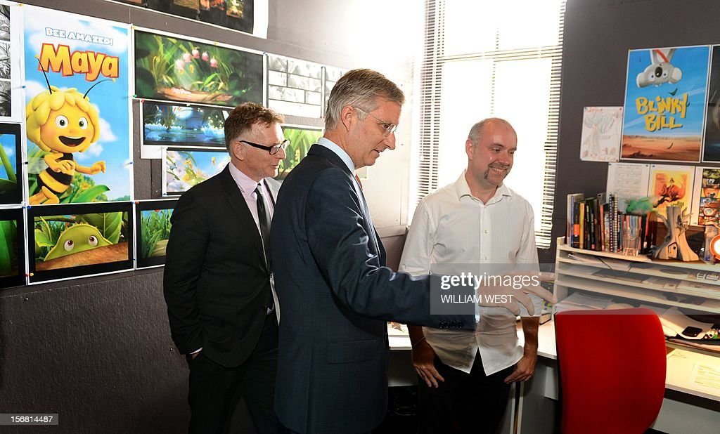 Prince Philippe of Belgium (C) looks at the animation on the screens as he talks to members of the creative team during a tour of Flying Bark Productions in Sydney on November 22, 2012. Philippe is on an 11-day mission to Australia and New Zealand to strengthen economic and trade ties. AFP PHOTO/POOL/William WEST