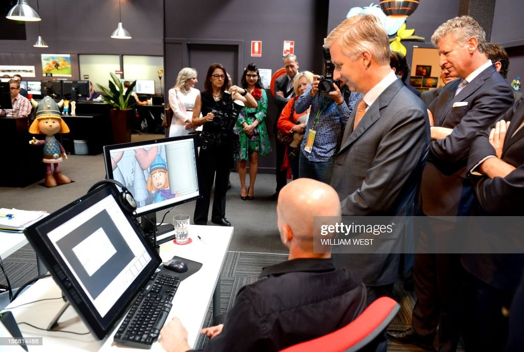 Prince Philippe of Belgium (2nd R) looks at the animation on the screens as he talks to members of the creative team during a tour of Flying Bark Productions in Sydney on November 22, 2012. Philippe is on an 11-day mission to Australia and New Zealand to strengthen economic and trade ties. AFP PHOTO/POOL/William WEST