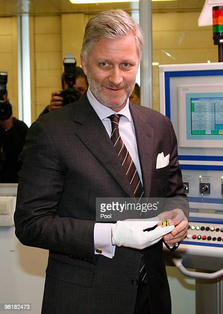 Prince Philippe of Belgium poses with a 100 euro coin at Belgiums Royal Mint on April 1 2010 in Brussels Belgium The golden 100 euro coin with a...