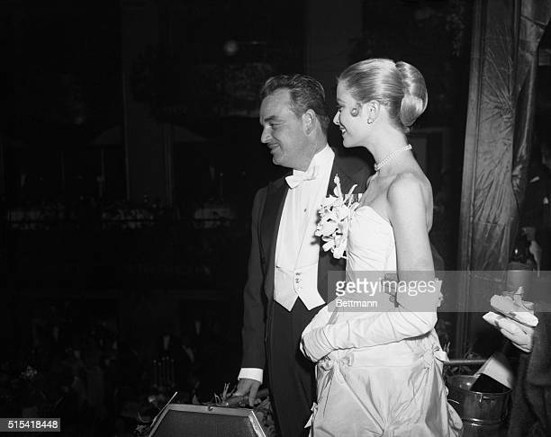 Prince Rainier III of Monaco and his bethrothed actress Grace Kelly stand together on the balcony during the Night in Monte Carlo Ball at the Waldorf...