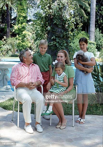 Prince Rainier III of Monaco sitting in a garden with his wife the American actress Grace Kelly and his children Albert Caroline and StTphanieMonaco...