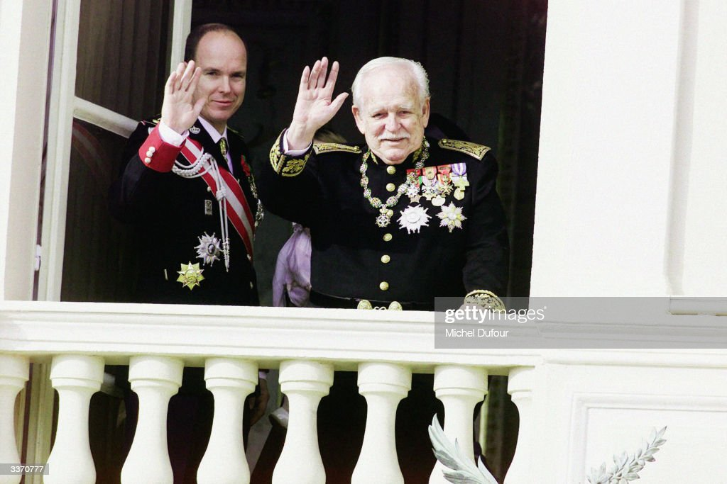 Prince Rainier III of Monaco waves from the balcony of the palace with his son Prince Albert celebrating principality's National Day on November 19, 2001 in Monte Carlo, Monaco.