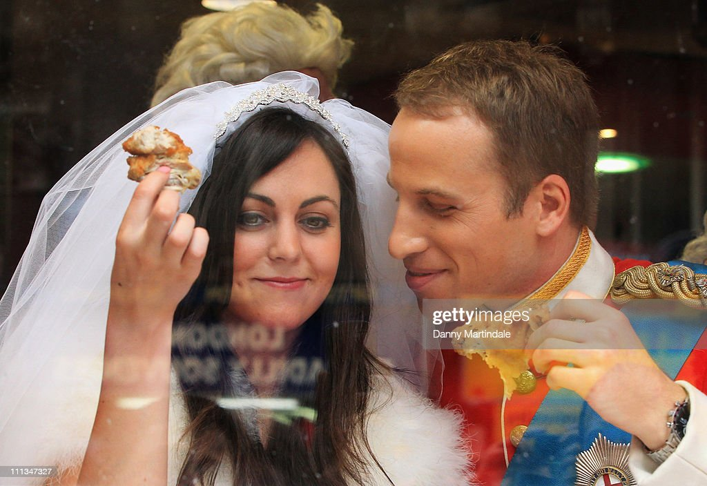 Prince William and Kate Middleton lookalikes Simon Watkinson and Jodie Bredo eat chicken in the window of KFC Leicester Square to mark the launch of...