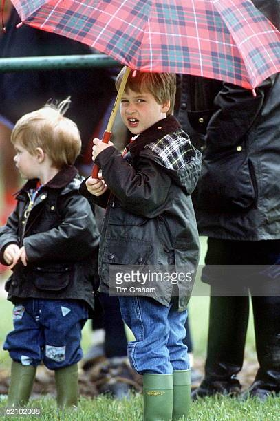 Prince William And Prince Harry At A Polo Match In Cirencester With An Umbrella Wellington Boots And Barbour Style Jackets In The Rain