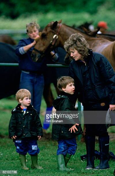 Prince William And Prince Harry Dressed In Barbour Style Waxed Rain Jackets And Jeans With Wellipet Wellington Boots Talking With Their Nanny Ruth...