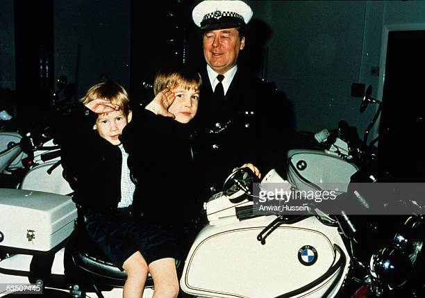 Prince William and Prince Harry give a royal salute from atop a police motorbike during a visit to the poloice force in November 1987 in Windsor...