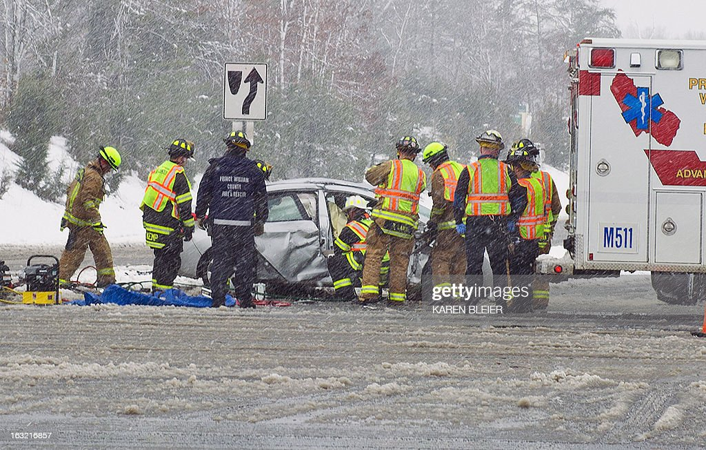 Prince William County rescue squads work to help a car accident victim out of the wreckage March 6, 2013 in Prince William Coutny, Virginia. The accident was likely caused by icy conditions and blowing snow due to the winter storm on the East coast.AFP PHOTO/Karen BLEIER