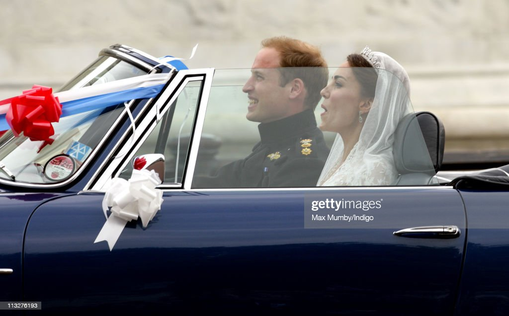 Prince William, Duke of Cambridge and Catherine, Duchess of Cambridge leave Buckingham Palace after their Wedding reception in Prince Charles' vintage Aston Martin DB6 Volante on April 29, 2011 in London, England.